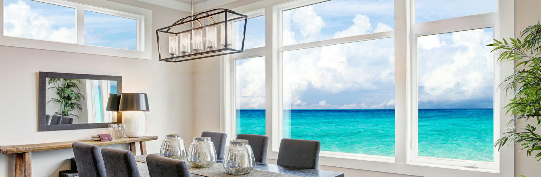 A beautiful kitchen with a gorgeous view of the ocean through impressive looking windows.